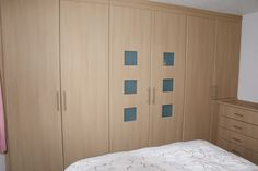 Fitted wardrobes with window panels in a natural wood finish.  #bedroom #furniture