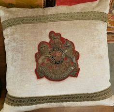 Ivory pillow with emblem, $250.  Gaslamp Antiques Too, booth T707.