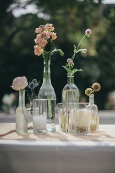 love the use of the different sized bottles to insert little flowers here and there - I do this in my house all the time and it makes me so happy!