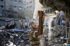 GAZA CITY : A Palestinian man helps remove a bag of flour from a house that was destroyed by an Israeli airstrike in Gaza City on August 21, 2014. The owners of the house were warned by the Israel army over the phone to leave their home minutes before a missile destroyed it. No one was phisically hurt in the incident.  AFP PHOTO/ROBERTO SCHMIDT