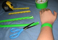 How to make a slap bracelet: 1- cut a 6in strip from a metal tape measure with old scissors. 2-curve edges. 3- cover in duct tape and trim edges again. 4- work it around so it naturally rolls. 5- go slap someone with it!  Thanks to my sweet boy for the tutorial!