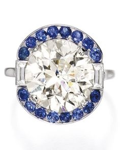 An Edwardian platinum, diamond and sapphire ring, Whitehouse Brothers, circa 1910. Centring a round diamond weighing 8.23 carats, framed by sapphires, further accented by baguette diamonds, with maker's mark.