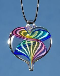 Glass Heart Pendant--A swirling spectrum of color is frozen in time at the heart of this crystal pendant suspended from a leather cord. Due to the handmade nature, slight variations occur, giving it a look all its own.