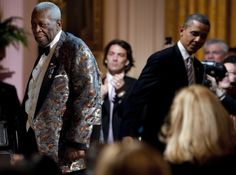 """US President Barak Obama (right) departs after helping Blues musician B.B. King (left) to the stage during a celebration of Blues music and in recognition of Black History Month as part of their """"In Performance at the White House"""" series in Washington, DC, February 21, 2012. — AFP pic"""