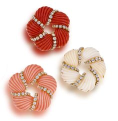 A set of three coral and diamond pendant brooches each designed as a spiral of carved and ribbed white, orange-red, and pinkish-orange coral sections, accentuated by full-cut diamonds, mounted in 18 karat gold.