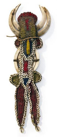 Karahut from the Maprik people ~ East Sepik Province, Papua New Guinea | Woven cotton figure with pair of pig tusks attached as double horns; accented with cowrie shells and red, blue and yellow natural pigments. | Est. 1,000 - 1,500$