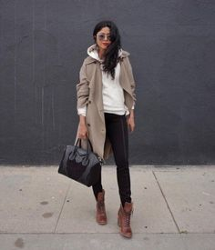 A trench coat over a hoodie, jeans, and lace-up boots.