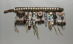 Girl's Belt Set Date: ca. 1884 Geography: United States, Oklahoma Culture: Southern Cheyenne Medium: Commercial and native-tanned leather, German-silver conchos, glass beads, metal cones, cowrie shells, brass beads, bone, deer tails, pigment, shell, wooden bead, brass gear, metal key