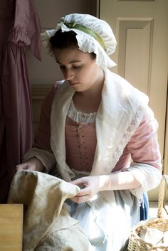 Servant girl in the Williams household, Colonial Williamsburg - Servant or housewife, sewing would be a regular chore, and leisure activity, in the 18th century.