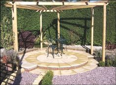 A circular paved seating area with a pergola shelter in a garden designed by Steve Rice, Blooming Good Gardens