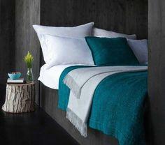 couleur murs gris anthracite, revetement sol noir, couverture et coussin bleu petrole, bûche décorative en guise de table de nuit