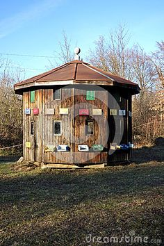 Photo about An image of a unique octagonal two story beehive house with many entrances on each side of the house decorated with painted flowers. Image of beehive, building, entrances - 89873909 Bee House, Flower Images, Permaculture, Gazebo, Entrance, Outdoor Structures, Painted Flowers, Beehive, Honey