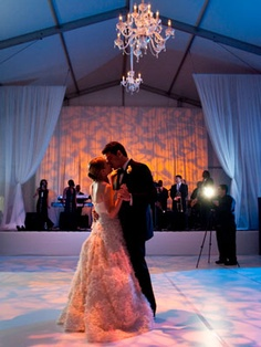 The patterned lights on the dance floor and over the band help to set the mood for this gorgeous first-dance moment.