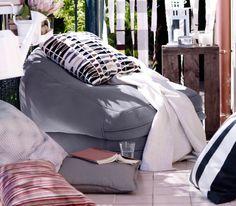 Ein BUSSAN Sitzsack für drinnen/draußen in Grau auf einem Balkon, darauf ein Kissen und eine Decke