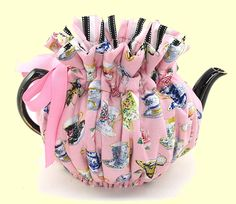 A pretty pink tea cozy covered with teacups.  Notice the striped lining.  So cute ...... an useful.