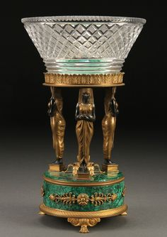 A FRENCH EMPIRE MALACHITE AND GILT-BRONZE STAND, 19TH CENTURY.  With three standing Egyptian female figures above a circular malachite base with gilt bronze feet supporting a diamond cut glass flared conical ring. Height 11.5 inches (29.5 cm).