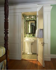 Gil Schafer designed wardrobe cabinet to disguise 3 ft. bathroom (see next pin w/picture of wardrobe) // love the bedroom's green walls against white wardrobe // bathroom wallpaper is 'Adelphi'