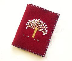 This embroidered wool felt needle book is approximately 3 1/2 wide x 4 1/4 long. Made from dark red wool felt and embroidered with a tree of life design embellished with green and white glass beads and edged with robins egg blue cotton floss. This needle holder contains two soft white wool felt pages for storing your needles on. The ties are very pale pink organza ribbon.  This would make a lovely gift for Mothers Day or for anybody who sews or collects needle books.  Ready to ship now.  To…