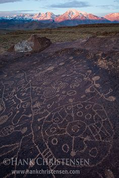 The mountains of the Eastern Sierra Nevada glow red over the Sky Rock Petroglyph, just outside of Bishop, California