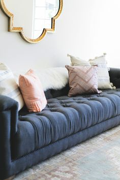 cozy tufted sofa paired with pastel prints and fur Photography : Monica Wang Read More on SMP: http://www.stylemepretty.com/living/2016/10/14/this-bachelorette-has-the-winning-combo-for-a-stunning-living-room/