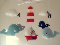 ((( INCLUDES )))  This nursery mobile contains 4 whales , 1 boat, 1 lighthouse, 2 clouds and 2 sea gulls. They are suspended from a white wood hanger,