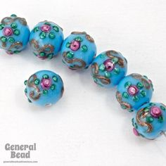 10mm round lampwork bead. Opaque blue turquoise with floral decor and gold swirl. Handmade, no two exactly alike. Made in the Czech Republic circa 1980's. Sold individually.