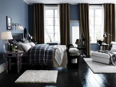 Mix for a Match: Using a rich deep blue wall color and lots of dark furniture in the bedroom creates a soothing retreat that envelops rather than cools. Accenting the walls, brown ceiling-height drapes and onyx-stained floors with pops of white and beige linens and area rugs throughout offers the perfect mix of masculine and feminine so often hard to achieve in a master.