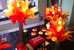 Table display with crepe paper bonfire with toasted marshmallows. Would be fitting for camping/woodsy theme party.  Was photographed at a fire engine party.