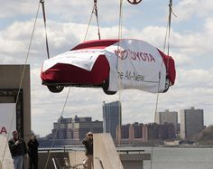 Not your normal delivery, a crane lifts a mystery Toyota model to the top level of the Javits Convention Center, appearing over the Hudson River and above Jersey City in the background, Monday, April 2, 2012 in New York in anticipation of its world debut to the media at the New York International Auto Show, Thursday, April 5. The car will usher in a new era of products from Toyota.  Photo: Joe Polimeni/Toyota #NYIAS