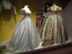 At right, 1850s party or evening dress. (Late 1860s dress at left.) Musée de la Mode et de la Dentelle, Brussels. Photo by Cristoph Houbrechts Vanhoorne.