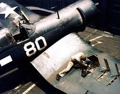 "Aboard the USS Block Island (CVE 106), a Marine ordnance man works on the .50 cal machine guns of a Vought F4U ""Corsair"" on one of the ship's elevators during operations off Okinawa - 5 June 1945 (USMC photo)"