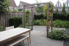 Kleine tuin met twee terrassen, natuursteen, basaltsplit en hardhouten vlonder.
