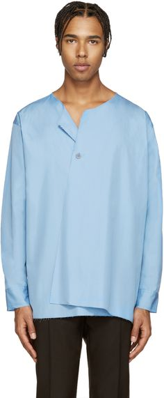 Long sleeve collarless poplin shirt in blue. Raw edges throughout. Single mother-of-pearl button closure at front. Single-button sleeve cuffs. Cinch strap at waist. Vent at sides. Tonal stitching.
