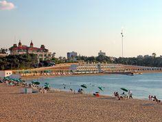 Vista do Palácio Hotel El Salamlek, visto ao fundo, e a bela praia em frente, para o Mar Mediterrâneo. Alexandria, Egito. O Palácio El-Salamlek, localizado na costa leste de Alexandria, foi construído pelo Khedive Abbas II do Egito em 1892, adjacente ao Palácio Real de Montazah.  Fotografia: Dennis Jarvis.