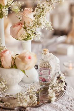 """These soft roses take on a fresh, simpler look when displayed stemless in white vases with baby's breath.  (via """"The Frosted Petticoat"""" in the pastel pink wedding gallery)"""