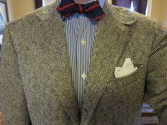 Light grey tweed jacket, white shirt with navy dress stripes, navy bow tie with red stripes