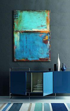 blauw kastje met kunst en vloerkleed met blauwe en groene strepen