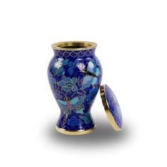 Skillfully crafted cremation keepsake utilizes the brilliance of blue enamel to create butterflies. Mini-urns are complementary keepsakes designed after larger