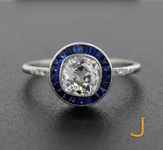 1.20 carat old mine cut diamond surrounded by 20 sapphires.