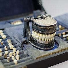 Singular c.1900 French dental molding case full of teeth and a stunning metal denture engraved VECABE with hinged jaws and removable teeth. The case is made of leather and when opened it reveals several compartments for display teeth. It is fully lined in blue silk velvet.