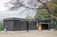 """Mukawa House by Studio Aula.  Lengths of black-painted timber clad this single-storey holiday home which steps across a wooded site in three volumes of increasing sizes. """"We created a few spots where the scenery visually breaks into the house in a sequence."""" http://www.dezeen.com/2014/11/24/studio-aula-mukawa-house-blackened-timber-japan/"""