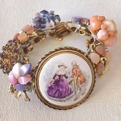 May I have this dance ... vintage assemblage bracelet Repurposed vintage ingredients: Vintage porcelain cameo, 1950s thermoset earrings, 60s beaded earrings & a vintage rhinestone brooch. All nestled on antique book chain & closes with a fold over clasp. Bracelet measures 7.5s. One of