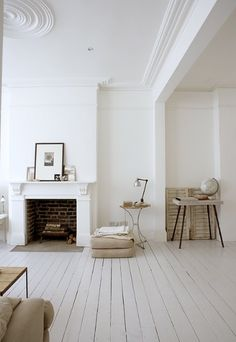 white floor white walls shabby chic minimalist distressed light airy ornate room fireplace