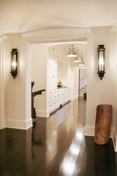 Hallway with dark wood floors, built-ins, wall lighting and pendant lighting | Thom Filicia