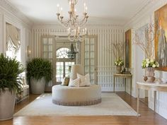 Large gorgeous entry. Love the striped walls, matching consoles and paintings, double simplechandeliers, matching urns with ferns. Horizontal moldings on lower walls add interest.