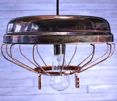 Reclaimed chicken feeder copper dipped and turned into light