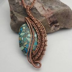 Pendant made of woven copper wire wrapped around a 3.5 x 2.25 cm ancient turquoise stone bead. Antiqued and hand-polished. Shipping to United States and Canada only.