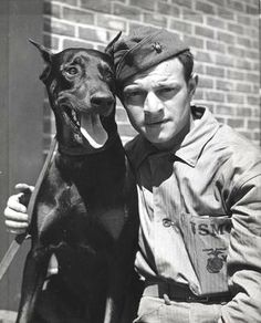 A doberman and a man in uniform...be still my beating heart.