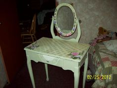 this is a jewelry vanity that I painted a light sage green in color, then hand painted a lattice pattern across the top, then hand painted cabbage roses on both the mirror's outer edge and table top. And painted half of a lace doily over the drawer to open as those it was drapped over it hanging out.