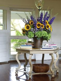 In the entry of a Southampton home, a rustic bucket holds a towering arrangement of sunflowers, lavender 'Monte Casion' asters, delphinium, and hydrangeas. Church Flowers, Funeral Flowers, Fall Flowers, Wedding Flowers, Fresh Flowers, Sunflower Floral Arrangements, Fall Flower Arrangements, Ikebana, Arte Floral
